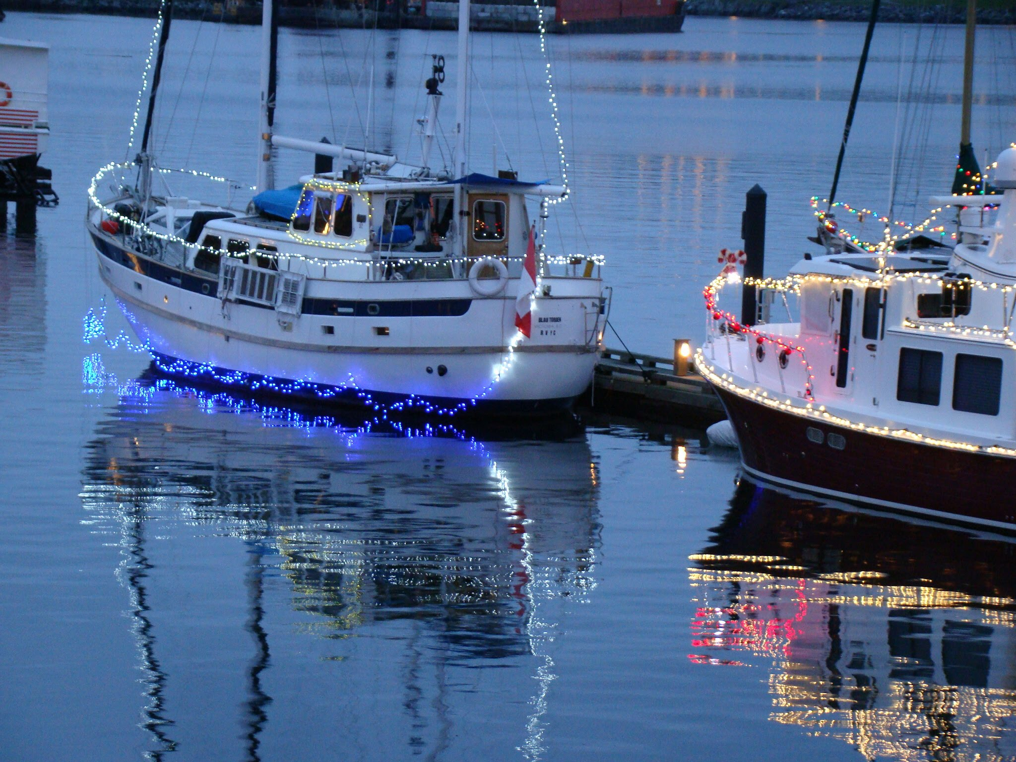 Boats in Victoria's Inner Harbour, decorated with Christmas lights reflecting in the water