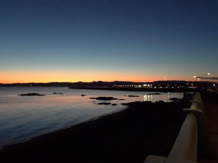 Sunset over the Ogden Point Breakwater with light reflecting off the ocean